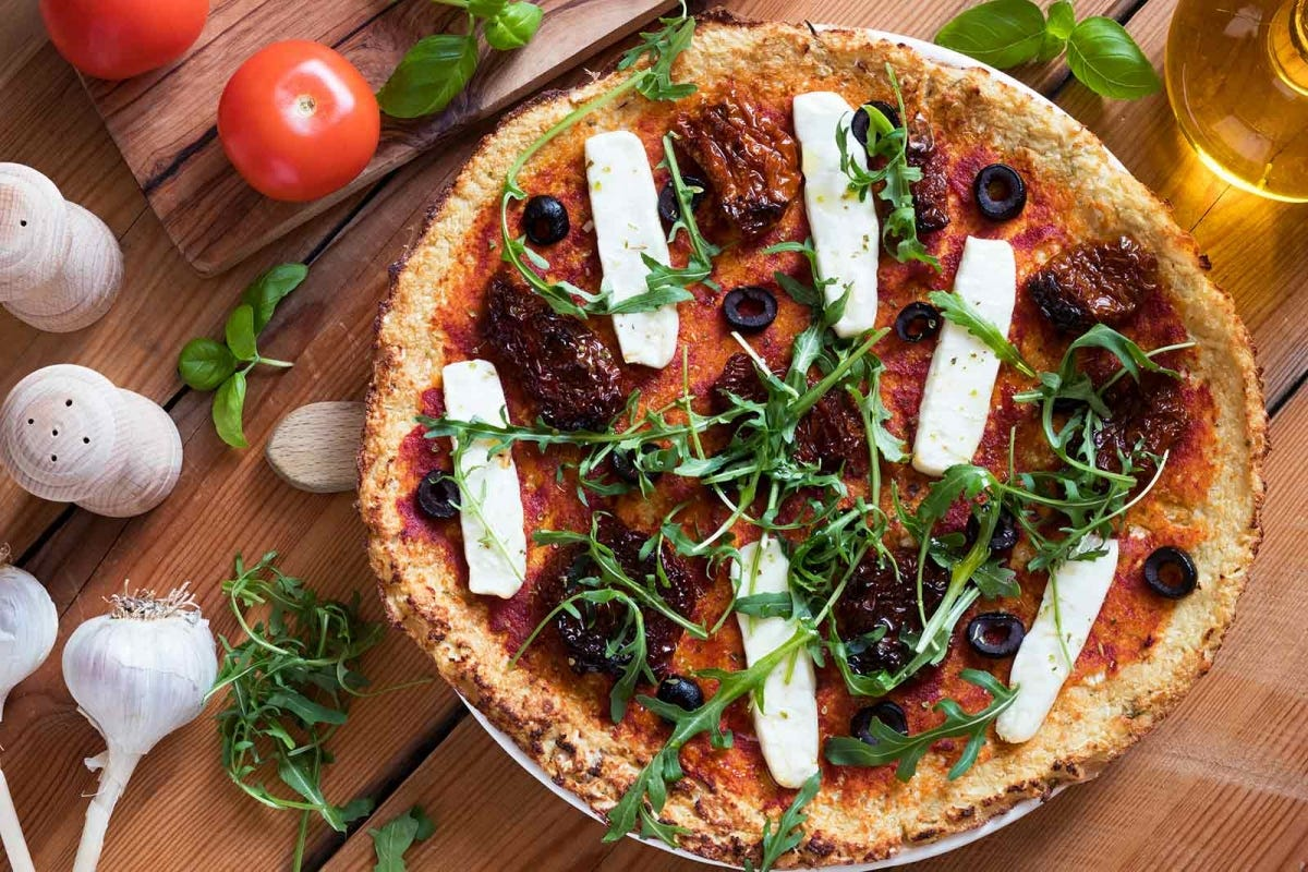 Gluten-free grain-free vegetarian pizza made from mashed cauliflower and almond flour, topped with sun dried tomatoes, olives, goat cheese and fresh arugula