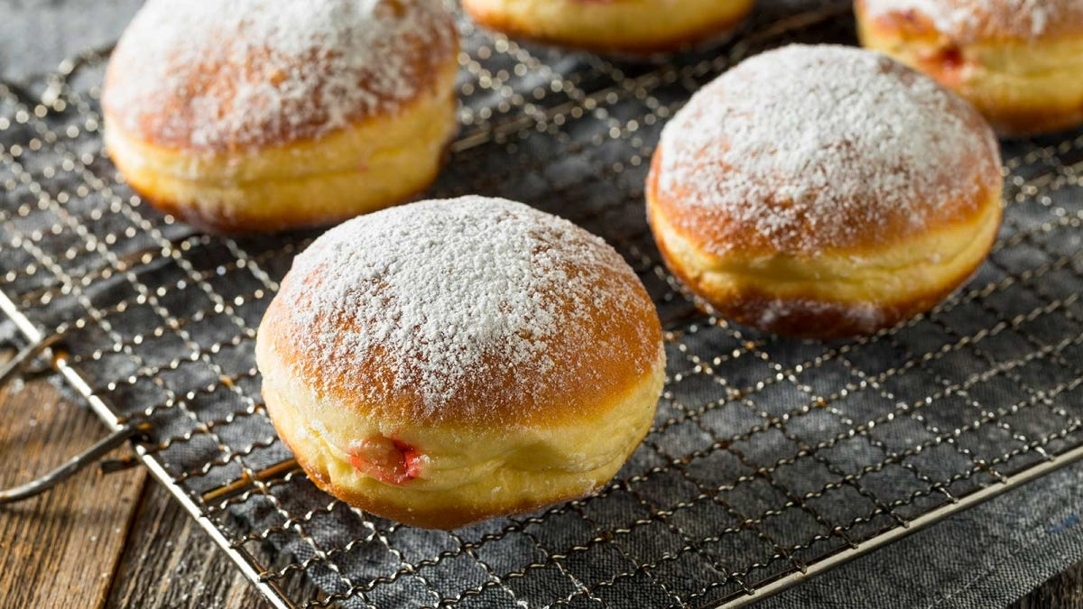 Paczski donuts on a wire cooling rack, freshly dusted with powered sugar.