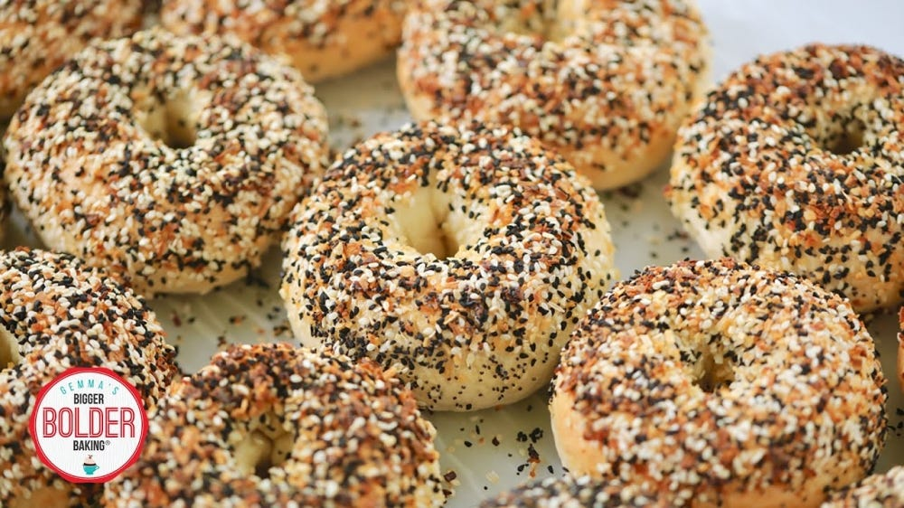 A soft focus photo of New York style bagels covered in salt and seeds.