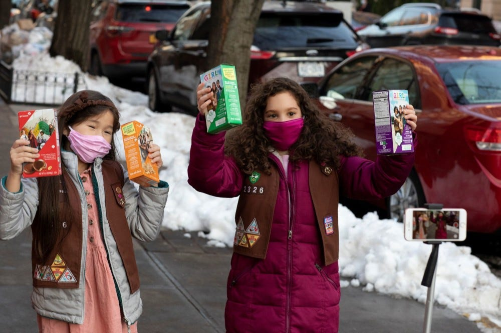 Two Girl Scouts wearing masks, and holding boxes of Girl Scout Cookies in each hand.