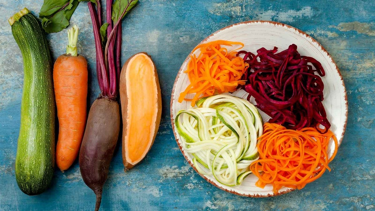 "A zucchini, carrot, beet root, and sweet potato next to a plate of ""noodles"" created from them."