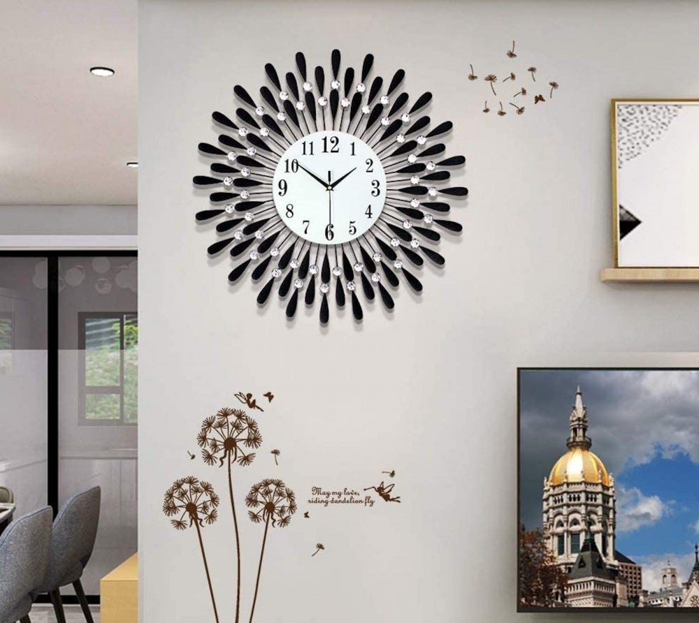 A wall clock surrounded with clear stones and black feather drops