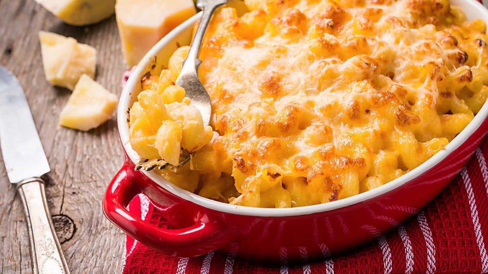 A red casserole dish, loaded with creamy macaroni and cheese.