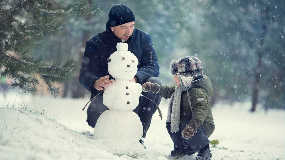 A father and his son playing in the snow, building a small snowman.