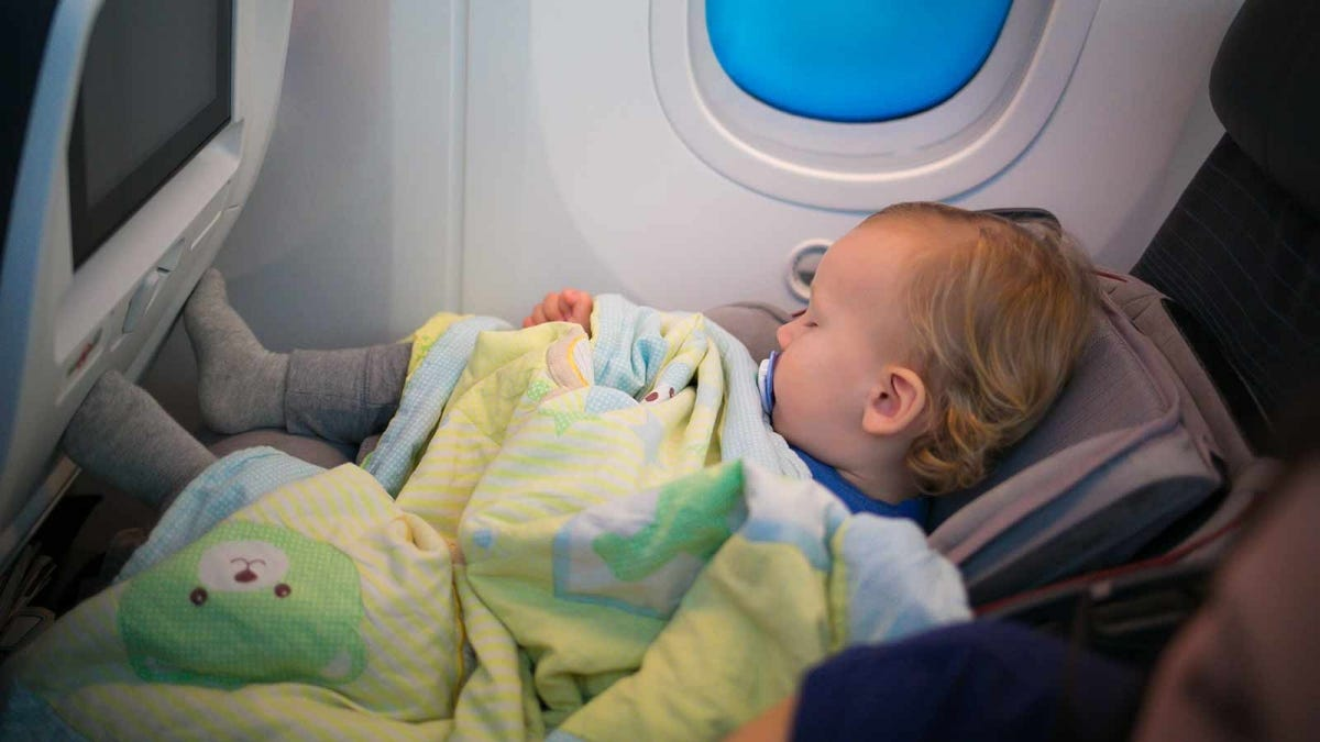 A toddler in a forward facing car seat in a window seat on an airplane.