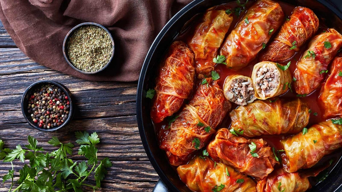 Cabbage rolls in a black pot, next to some bowls of spices on a wooden table.