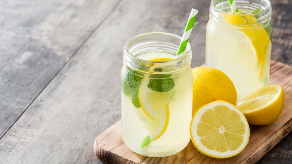 Freshly made lemonade in mason jars with striped straws.