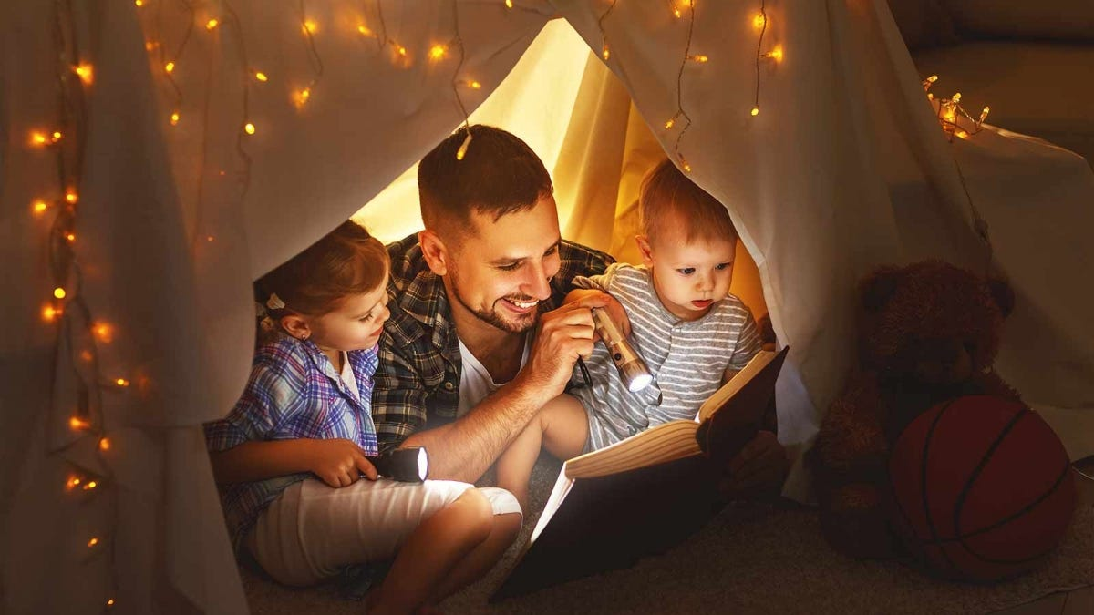 Man reads a book to his children in a blanket fort