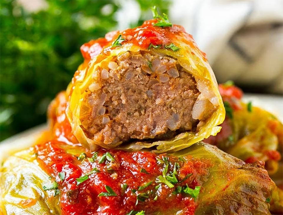 A plate of stuffed cabbage rolls stacked on top of each other.