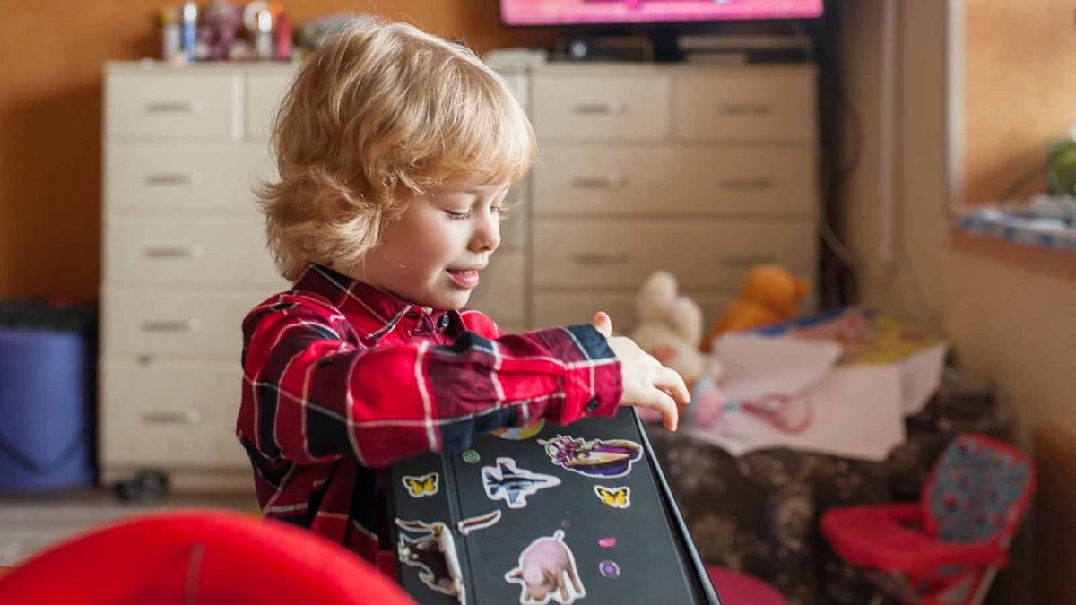 Young child applying stickers to a tablet cover while playing in a bedroom.