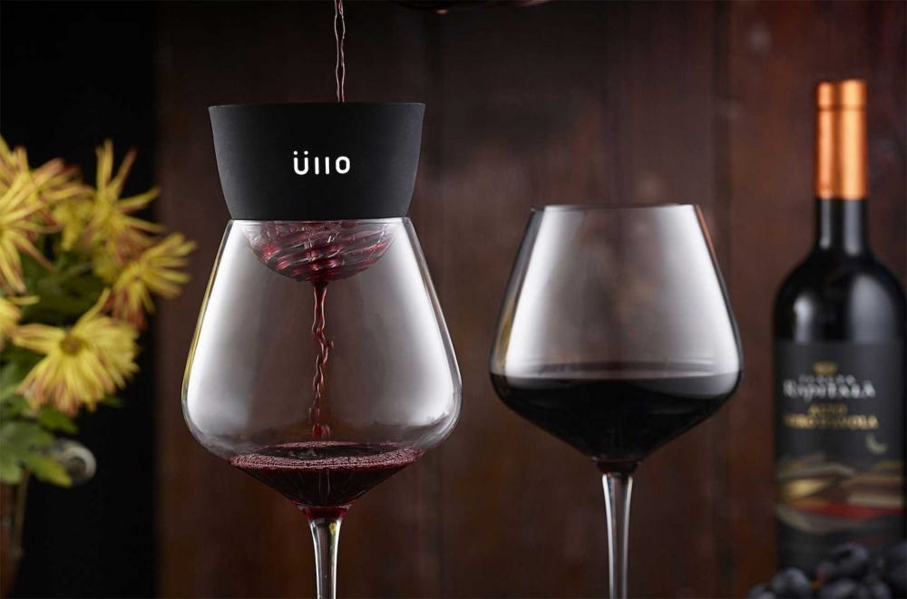 An Ullo wine purifier resting on a glass with wine pouring through it.