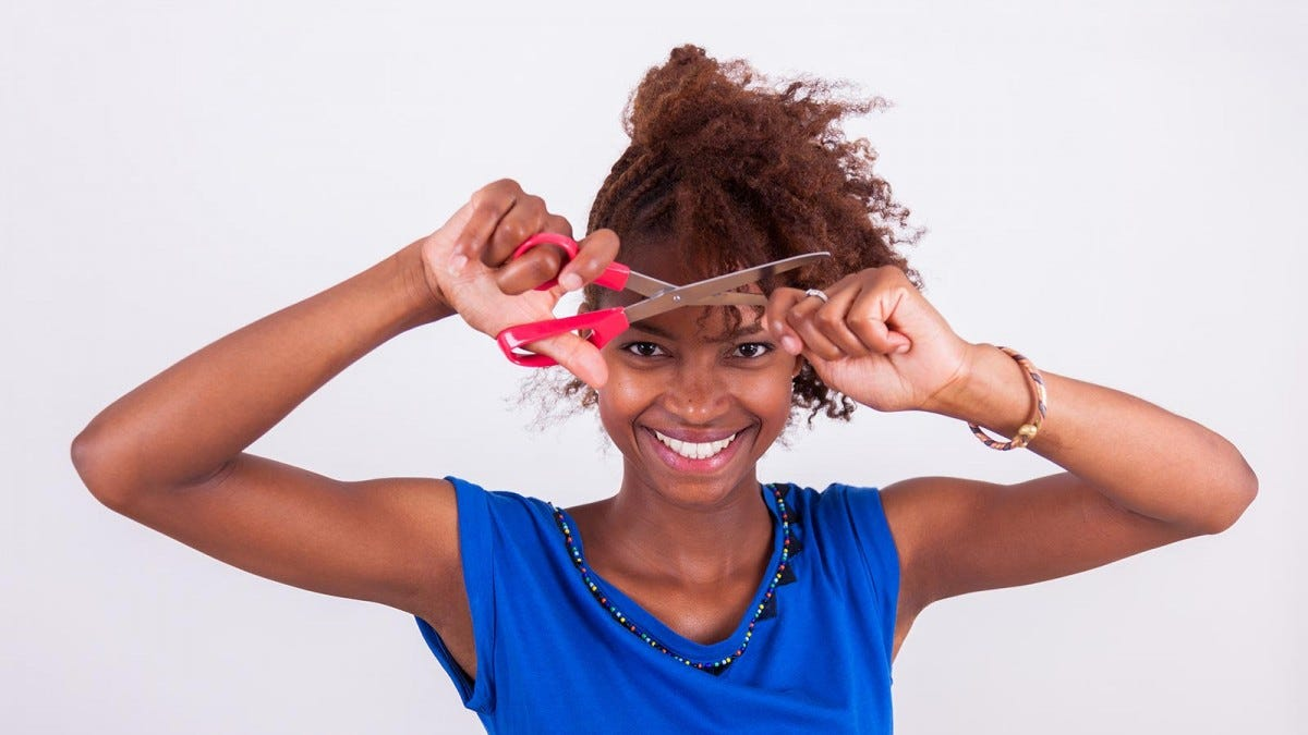 Woman with natural African hair cutting it at home.