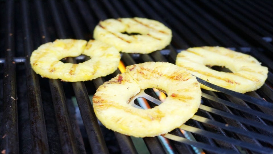 Grilling four rings of freshly sliced pineapple.