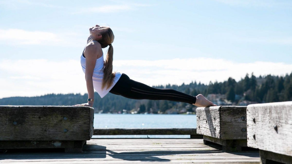A young woman doing upward-facing dog on a pier.