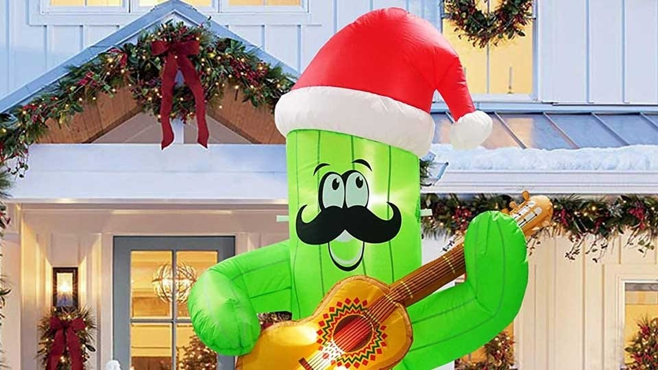 A 7-foot tall inflatable cactus wearing a Santa hat and playing a guitar.