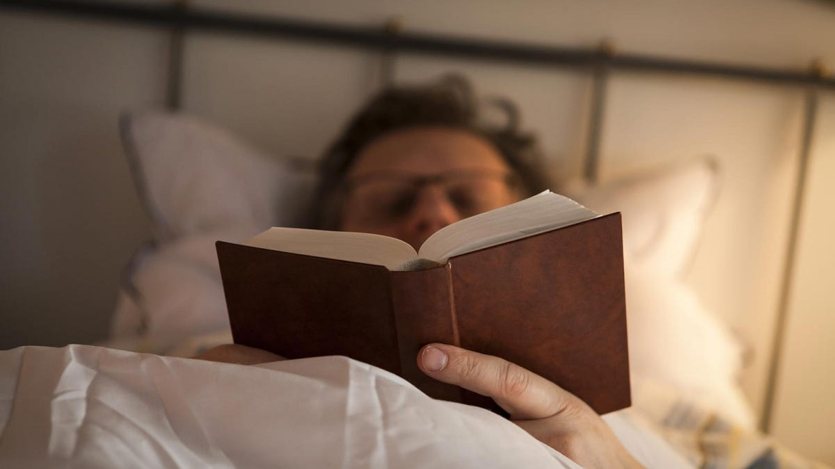 Man reading book in bed to help unwind at the end of the day.