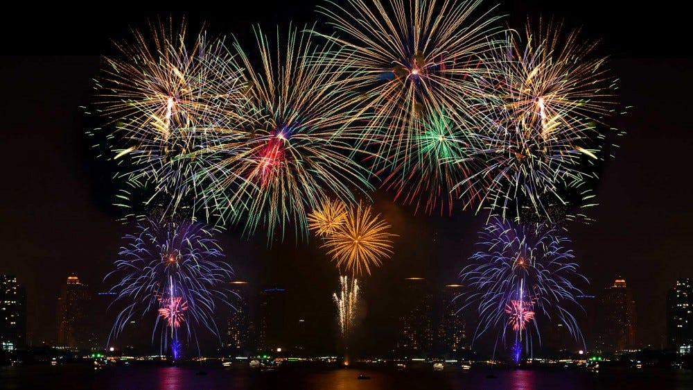 A fireworks show launched from barges floating on a river.