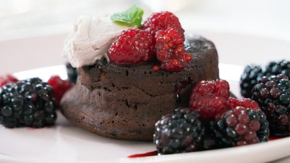 A piece of molten lava chocolate cake, topped with a fresh berry marscapone and warm berry cassis topping.