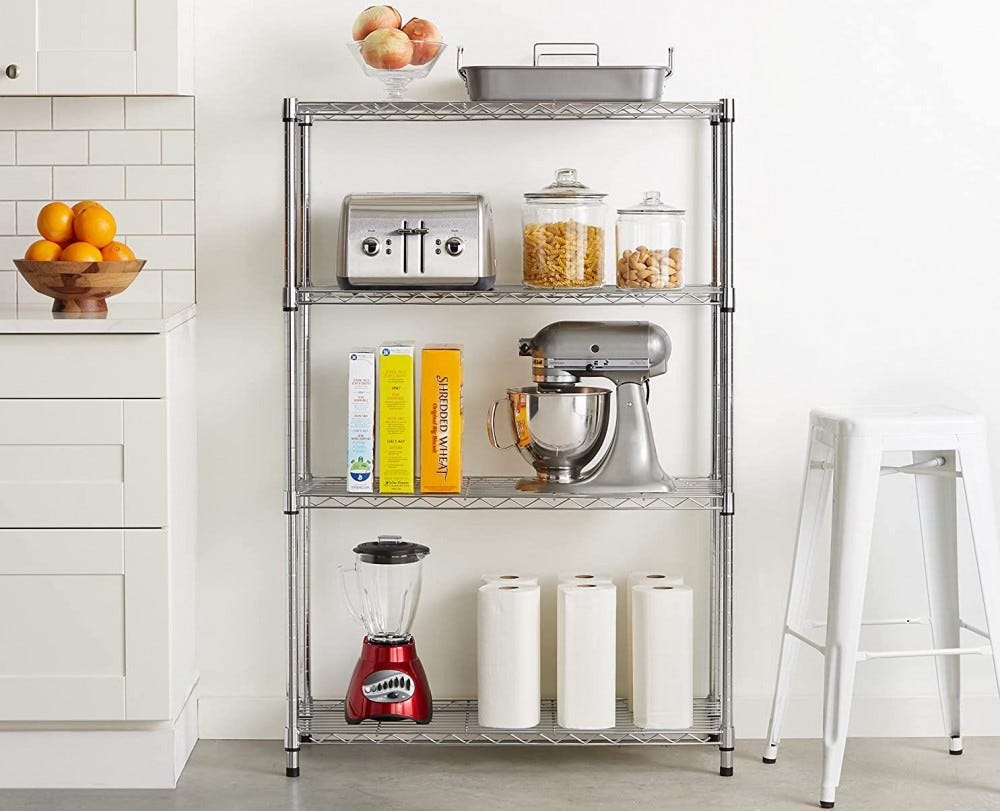 Silver wire shelving unit in a kitchen, holding appliances, books, and food jars