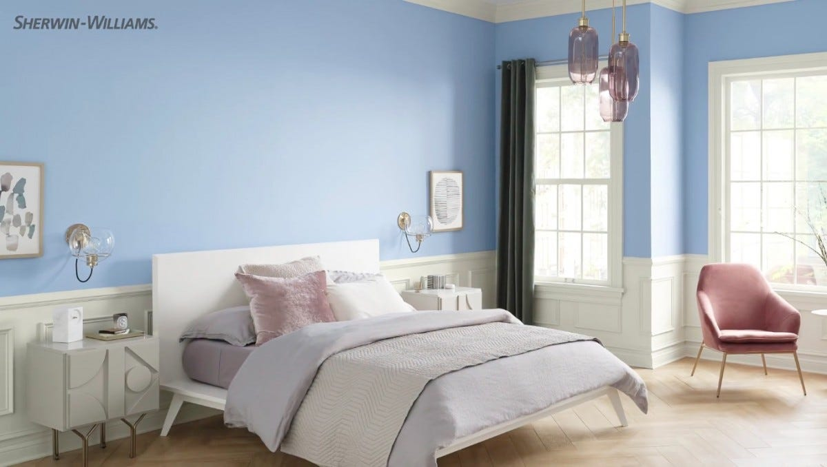 a bedroom painted a light blue with neutural accents