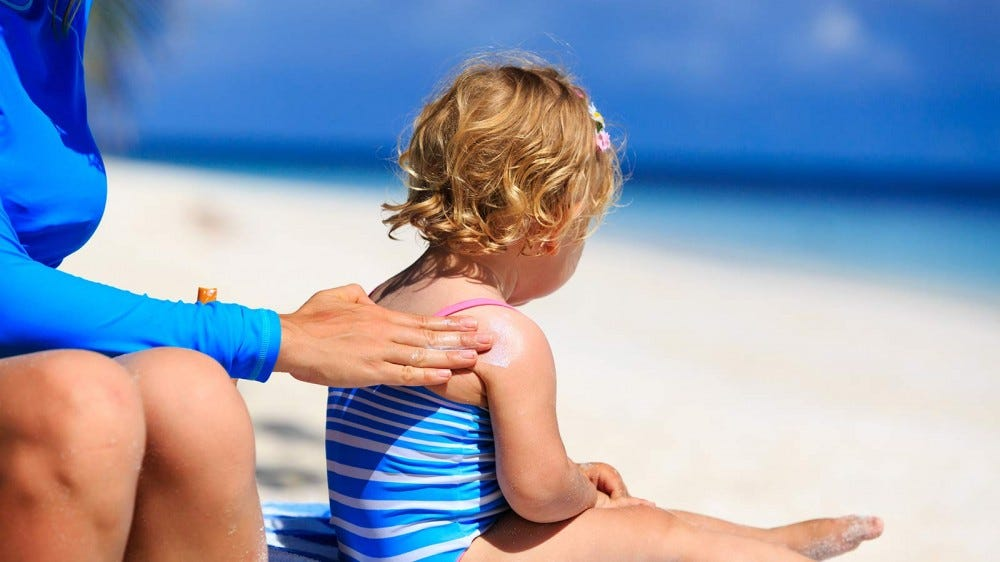 A mother applying sunscreen to a little girl's shoulder.