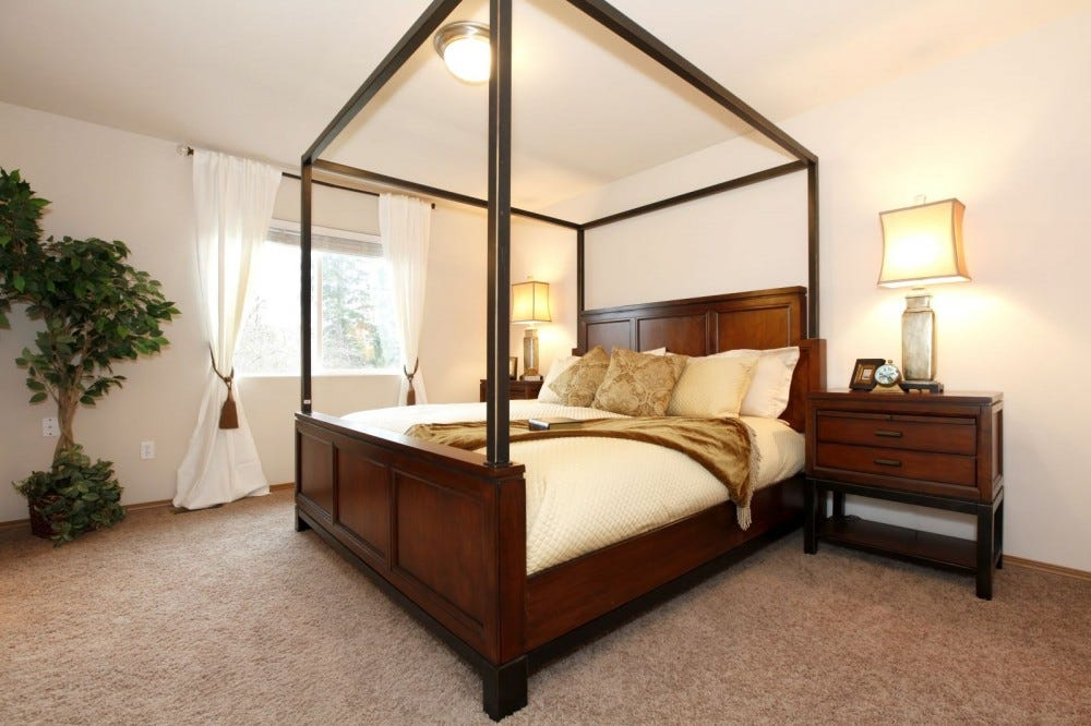 A large wooden canopy bed in a cream-colored bedroom.
