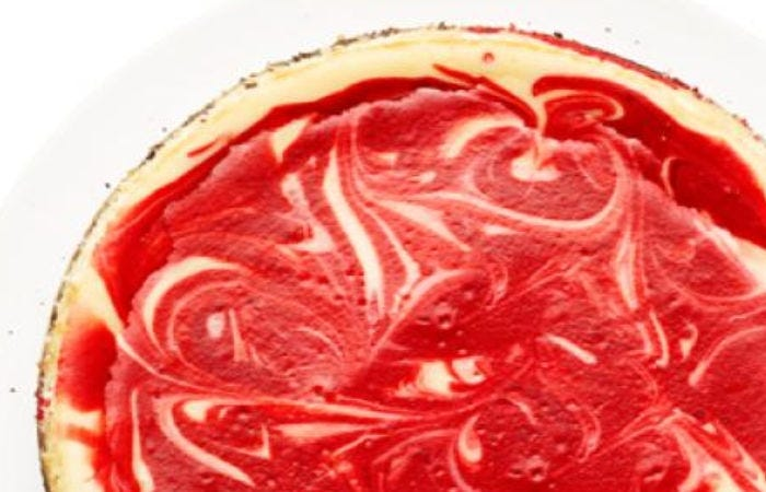 A top view of a swirled red velvet cheesecake.