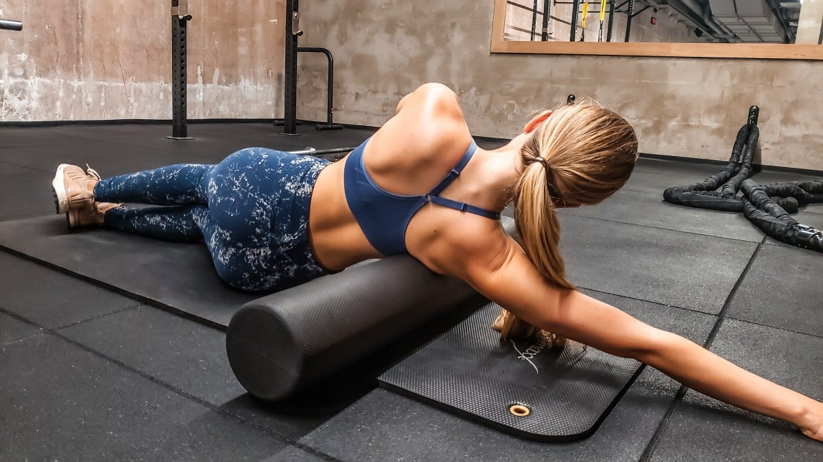 A woman in a gym with a foam roller under her right arm.