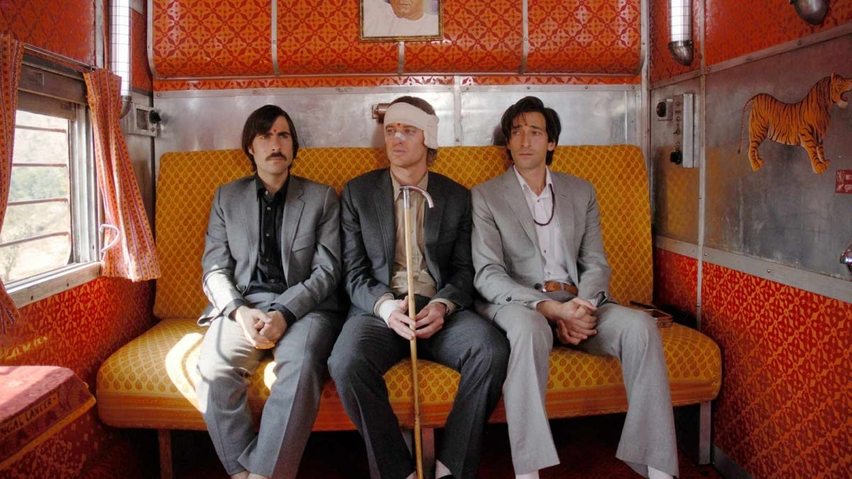 "Scene from ""The Darjeeling Limited"" with the characters sitting in an Indian travel train."