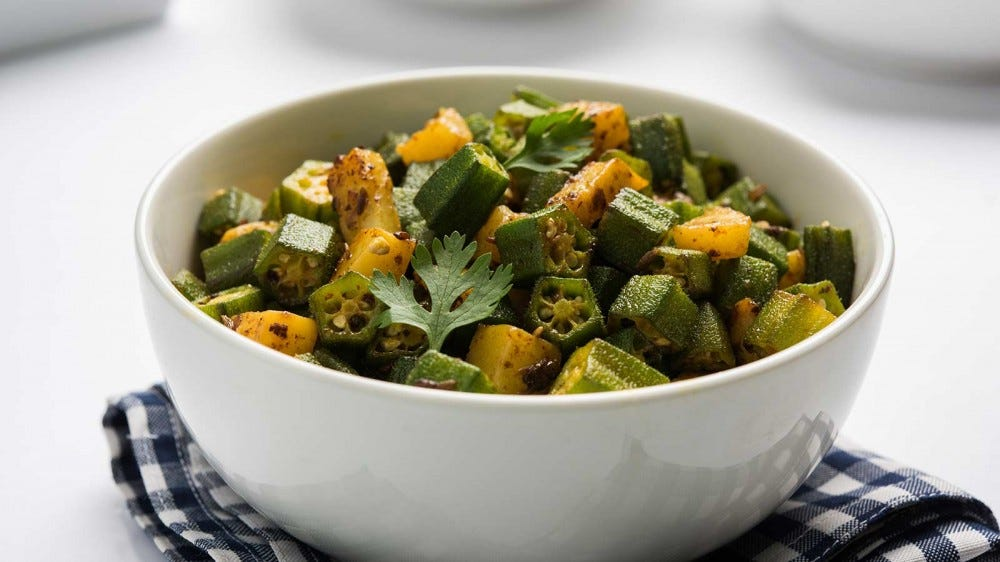 Indian-style fried rice and okra, served in a white bowl.