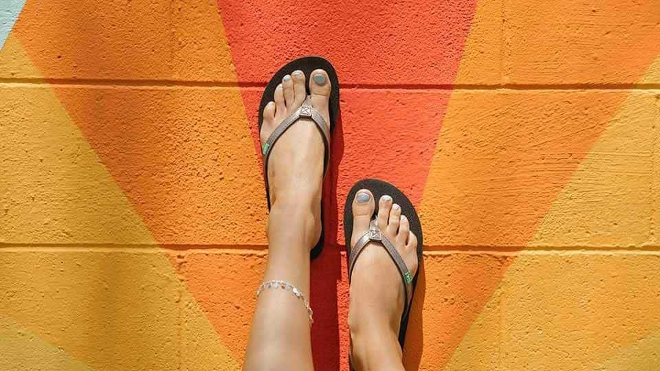 A woman wearing metallica Sanuk flip flops with her feet up on a colorful orange wall.