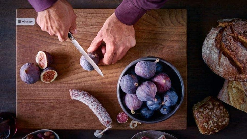 Someone slicing fresh figs with a Wüsthof eight-inch chef's knife on a cutting board.