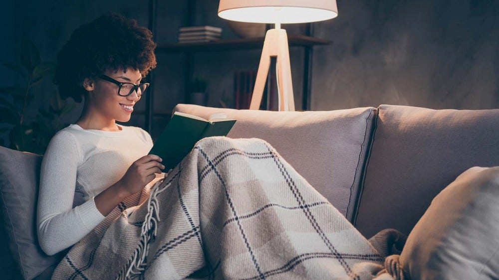 A woman reading a book on a sofa under a blanket.