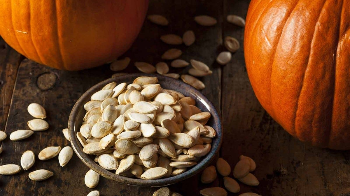 Pumpkin seeds in a bowl on a table next to two pumpkins.
