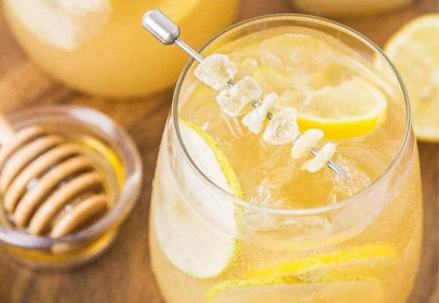 A tumbler full of Ginger Pear Bourbon, garnished with ginger, and pear and lemon slices.