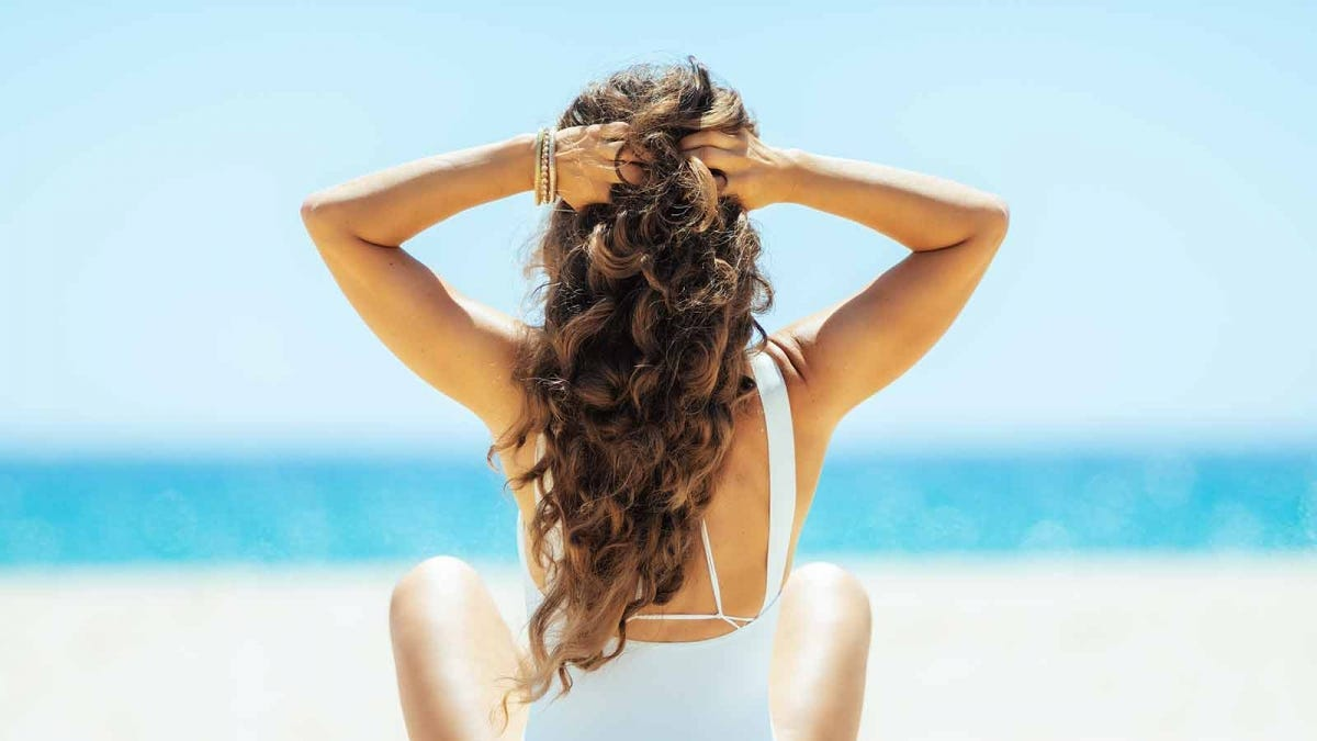 Back view of a woman with long, curly hair sitting on the beach.