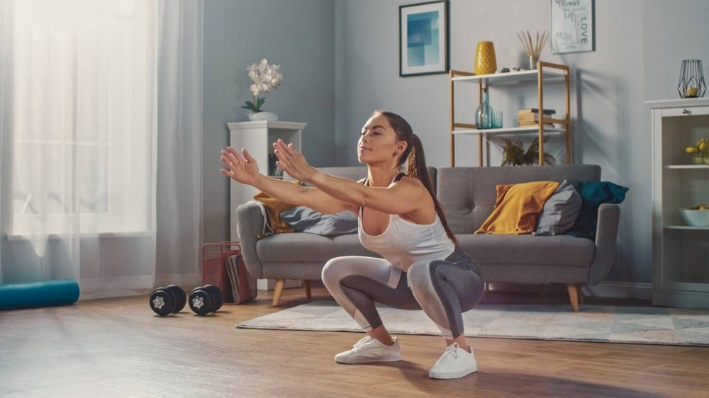 Woman doing squats in her living room.