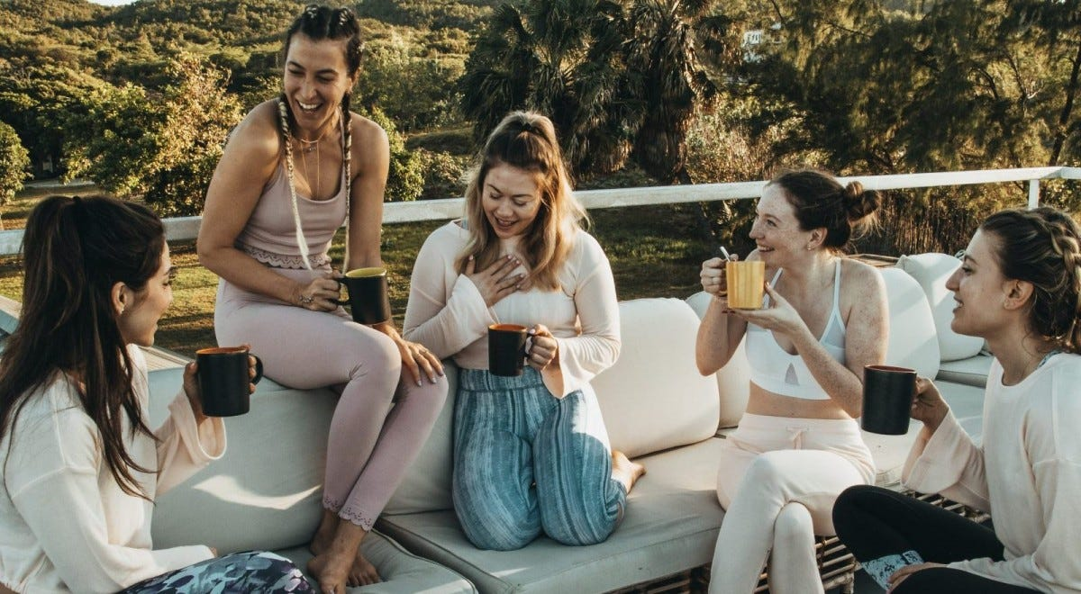 A group of women sitting on a balcony holding coffee mugs.
