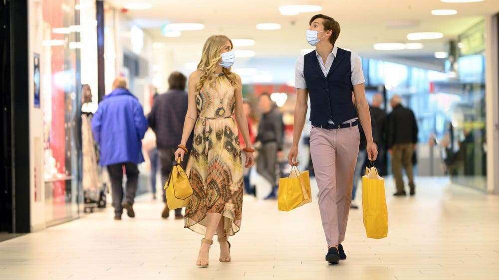 A couple shopping, wearing masks.