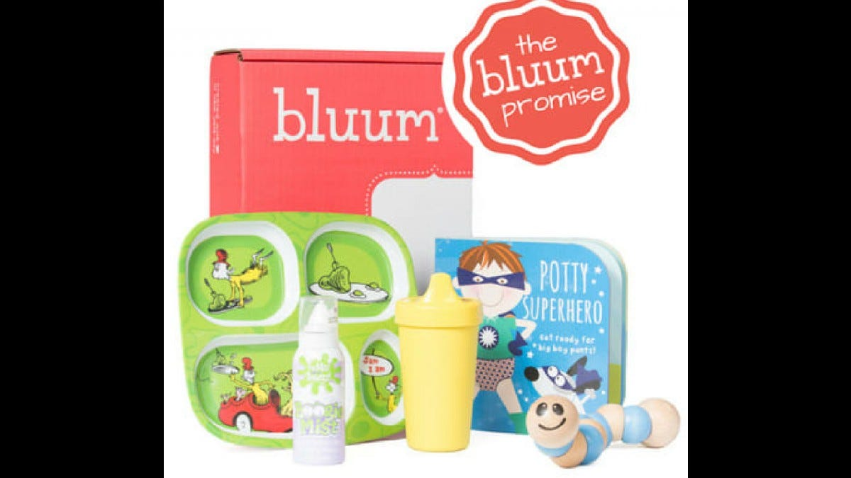 A Bluum box with a sippy cup, a book, a caterpillar toy, and a food tray with pictures on it.