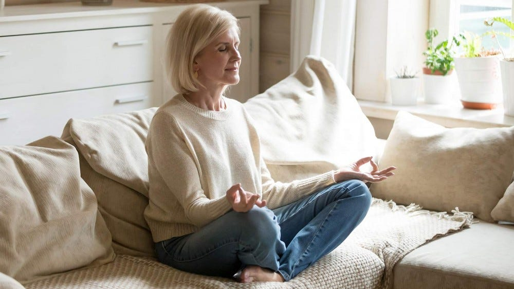 A woman meditating on a couch in a sunny living room.