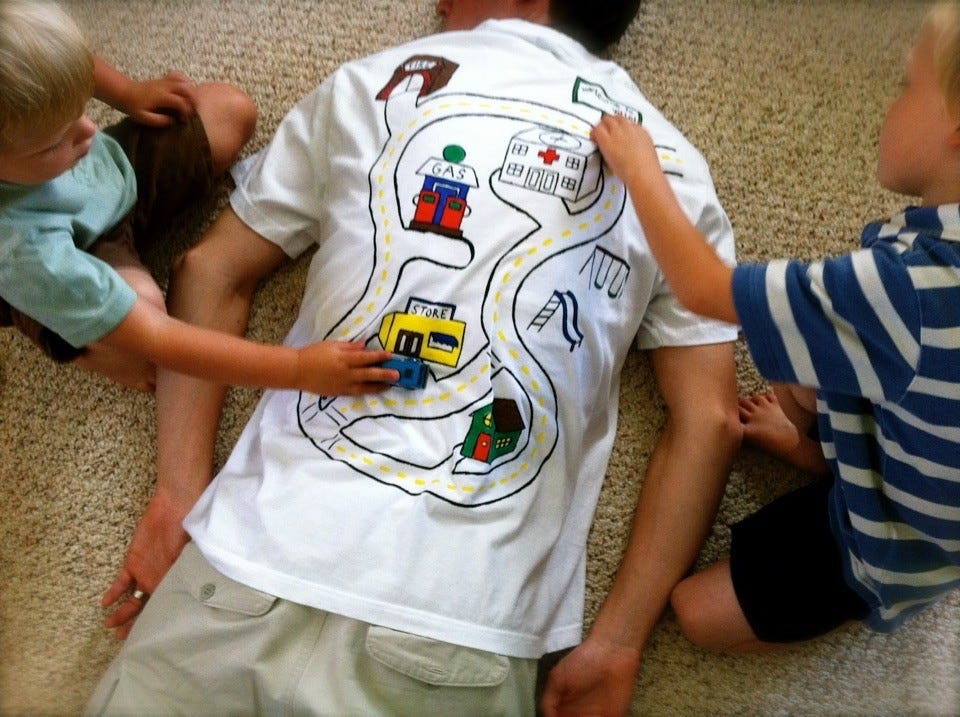 A man lying on his stomach while two young boys push cars on the road map on the back of his T-shirt.