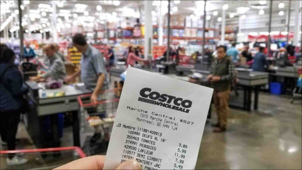 A Costco receipt being held in front of cash registers.