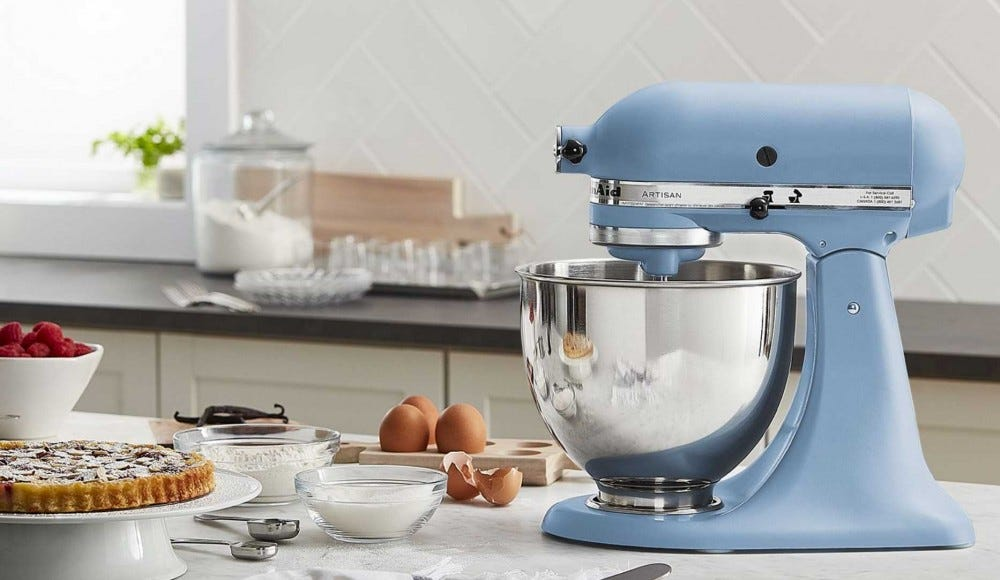 A 'Velvet Blue' Kitchenaid stand mixer sitting on a marble counter.