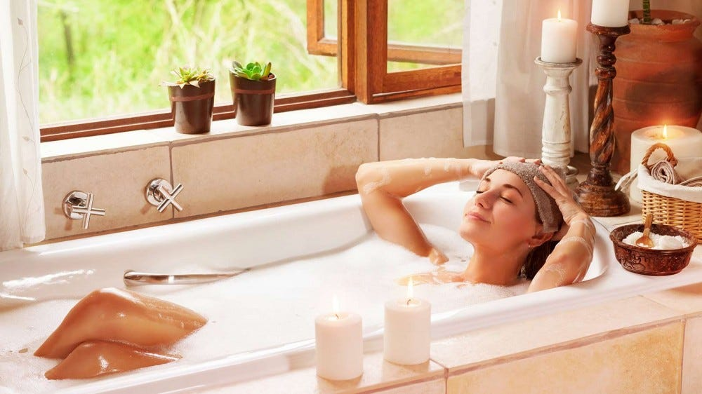 A woman soaking in a bathtub, surrounded by candles and plants.