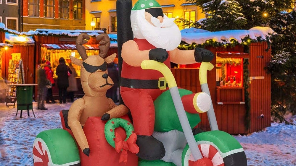 An inflatable Santa and reindeer set up for a holiday display.