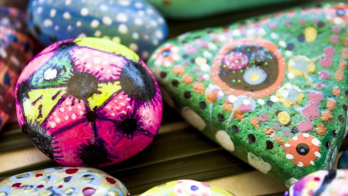 Brightly painted rocks adorned with patterns of lines, dots, and stars.