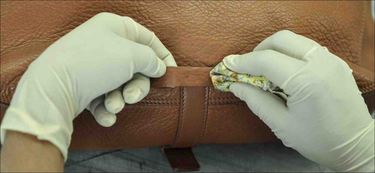 closeup of gloved hands applying conditioner to brown leather purse