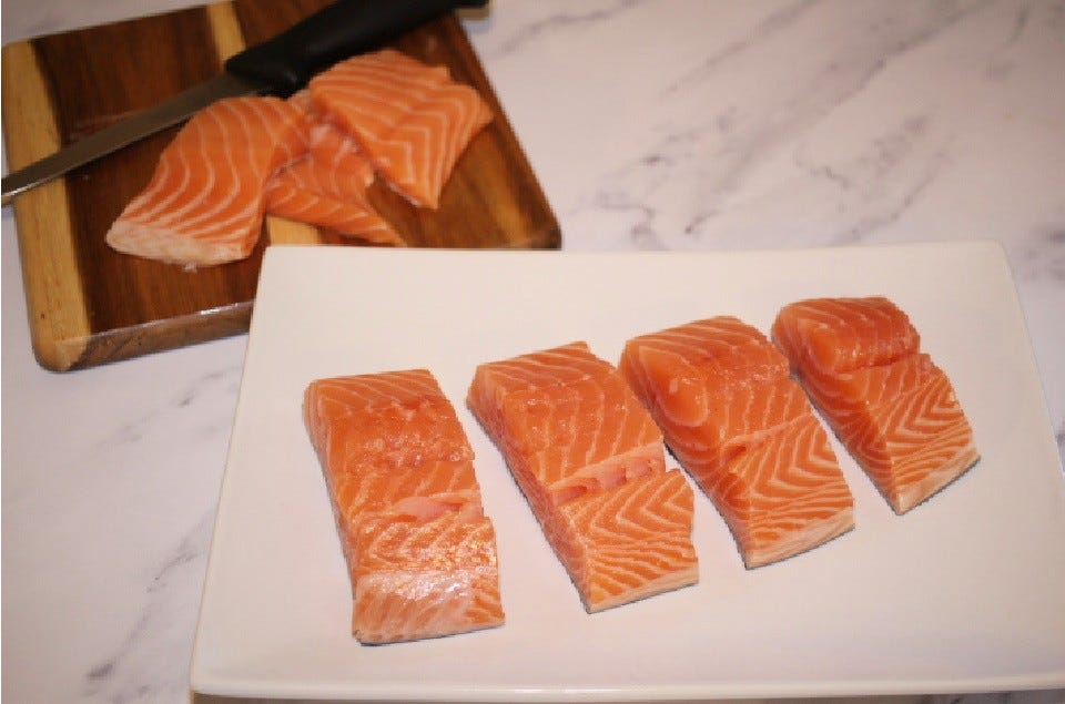 Four salmon filets, freshly portioned sitting on a rectangular plate with salmon scraps, a knife and a cutting board in the background.