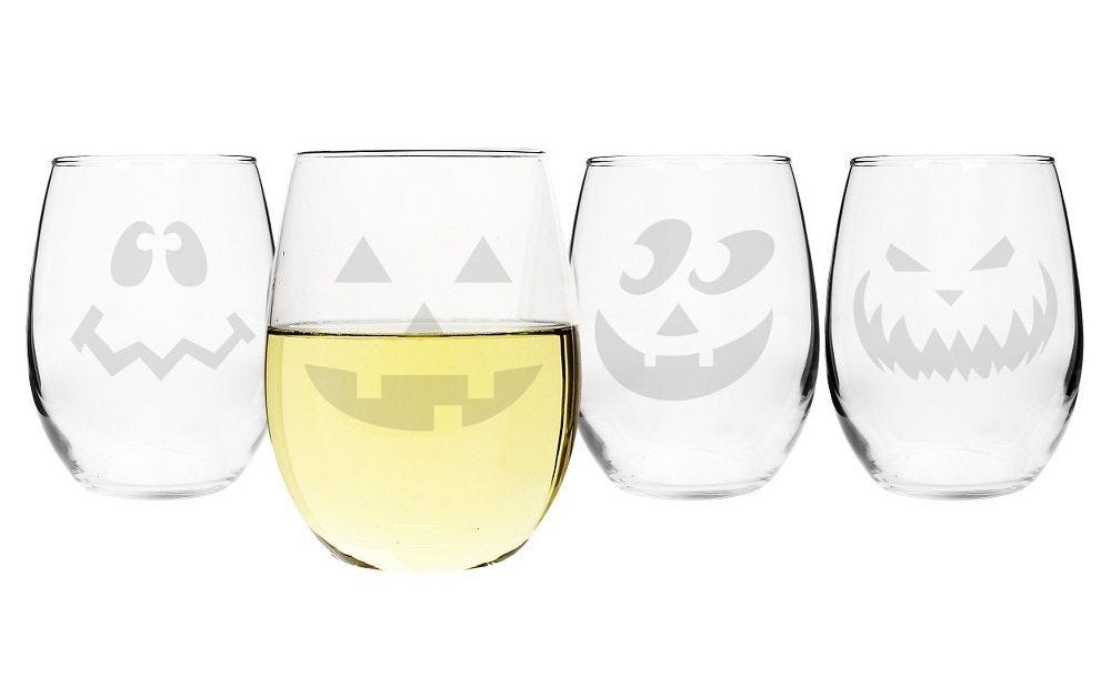 Four stemless wine glasses with jack-o'-lantern faces.